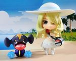 1girl bag beach blonde_hair blue_sky braid chibi cloud commentary_request cosplay dress figure full_body garchomp hair_over_one_eye hat lillie_(pokemon) lillie_(pokemon)_(cosplay) long_hair outdoors photo pokemoa pokemon pokemon_(game) pokemon_dppt pokemon_sm shirona_(pokemon) sky smile toy twin_braids